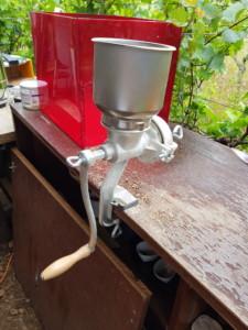 Moulin à céréales fixé sur un rebord de table, prêt à moudre le houblon pour préparer la bière.