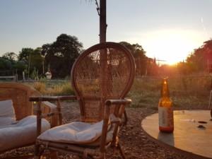 Une chaise en osier vide à côté de laquelle repose une bière prête à être dégustée, sur un magnifique fond de soleil couchant