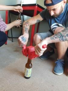 Une personne utilise un outil spécial pour fermer une bouteille de bière avec une capsule métallique
