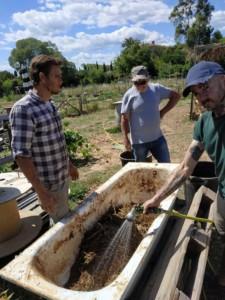 Trois hommes se tiennent debout autour d'une vieille baignoire dans laquelle repose un mélange de terre et de paille en préparation. L'homme de droite est en train d'arroser le mélanger avec un tuyau.