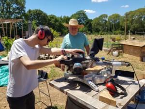 Deux personnes en train de découper un morceau de bois à l'aide d'une scie à onglet