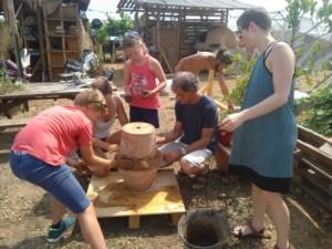Cinq personnes en train de souder deux pots de fleur en terre cuite avec de l'argile pour constituer un Oya