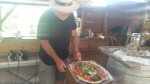 Un homme est en train de préparer une pizza avec des légumes frais dans la cuisine de l'Oasis