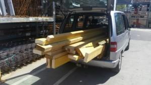 Transport de grandes planches de bois qui dépassent du coffre d'un véhicule gris
