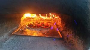 Pizza en train de cuire dans le four en terre-paille
