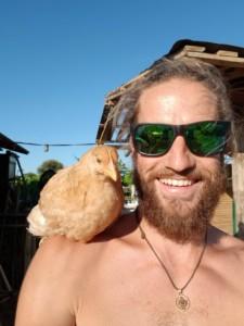 Un poulet tranquillement perché sur l'épaule de David qui sourit, fier comme un capitaine pirate et son perroquet