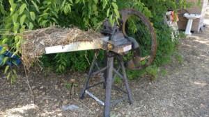 Un hache paille ancestral muni d'une manivelle pour actionner un mécanisme qui entraîne de la paille vers une lame en rotation