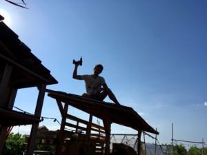 Un homme à contre jour assis sur le toit et brandissant une visseuse