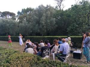 Une quinzaine de personnes assises sur des chaises regardent quatre acteurs et actrices en train de jouer une pièce entre deux rangées de haies taillées
