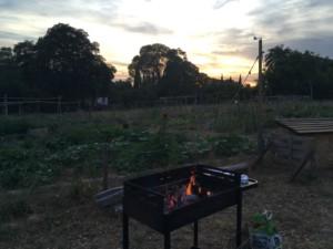 Un barbecue brûle devant les jardins de l'Oasis alors que le soleil se couche derrière les arbres en fond