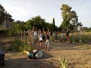 Séance de Yoga réunissant une dizaine de personnes au milieu d'un carré délimité par des bac de cultures