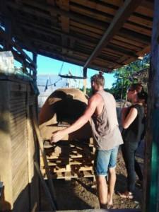 Deux personnes en train d'allumer le four en terre-paille