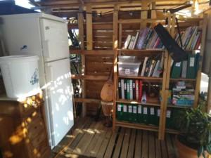 Photo du fond de la paillote de l'Oasis. Un frigo débranché sur la gauche sert de placard à semences et une bibliothèque bien rangée sur la droite.