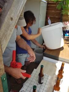Une personne vide le fond d'un tonneau en plastique blanc dans une canette en verre pendant qu'une autre personne sertit les précédentes canettes d'une capsule métallique.