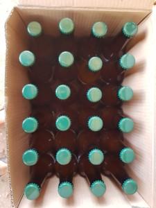 Carton de 24 canettes de bières vues du dessus. Elles sont de couleur brune avec un bouchon vert olive.