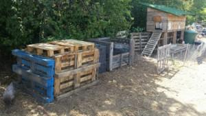 Zone de compostage près du poulailler (en fond). Les bacs sont bien rangés, le compost a été empilé proprement et protégé par des palettes.