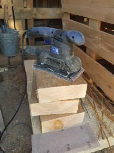 Tas de blocs de bois empilés sous une ponceuse à bande.