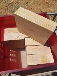 Huit blocs de bois d'environ 40 cm par 40 cm et d'une épaisseur de 10 cm dans une caisse rouge.