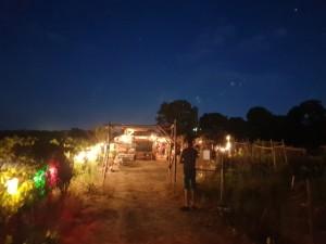Arche d'entrée de l'Oasis près de laquelle attend une personne dans l'ombre. Le ciel nocturne est d'un bleu profond, criblé d'étoiles.