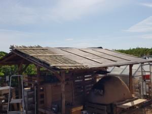 Toit au dessus du four en terre-paille partiellement recouvert de bambous alignés.