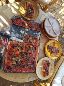 Grande pizza rectangulaire artisanale découpée en belles parts généreuses.