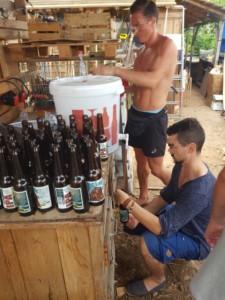 Deux personnes mettent une nouvelle cuvée de bière en bouteille.
