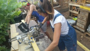 Deux personnes en train de couper une planche à l'aide d'une scie à onglet.