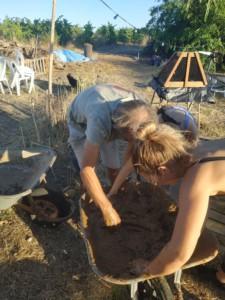 Deux personnes ont les bras plongés dans une brouette pour mélanger de la terre, de l'eau et de la paille.