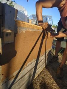 Une personne étale le mélange de terre, eau et paille sur le bord du séchoir solaire en une fine couche qui évitera à l'air de s'échapper entre les lattes de bois.