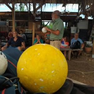 Une personne tenant une sphère blanche, symbolisant la Lune, en arrière plan d'une sphère jaune, symbolisant le Soleil, posée sur un sac.
