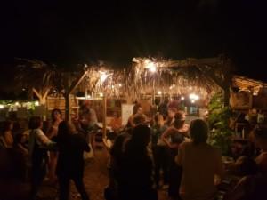 Paillote de nuit, remplie de personnes en train de discuter en petits groupes.