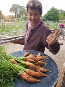 Germain pose le pouce en l'air avec un grand sourire derrière une table couverte de carottes tout juste cueillies.