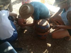 Trois personnes en train d'assembler des pots en céramique à l'aide de glaise pour créer des Oyas