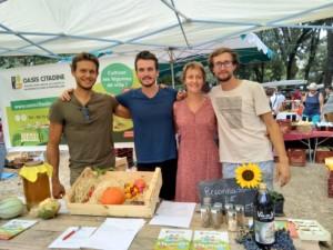 Quatre personnes se tenant côte à côté derrière le stand de l'Oasis à la fête de la tomate