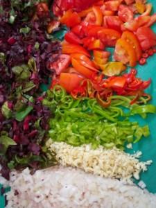 Composants d'une salade composée coupés en morceau et disposés côté à côté sur une planche à découper.